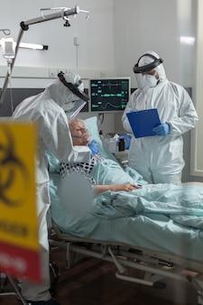 Pielęgniarka medyczna ubrana w kombinezon ppe nakłada maskę tlenową starszemu pacjentowi, w trakcie globalnej pandemii z koronawirusem, a lekarz robi notatki w schowku