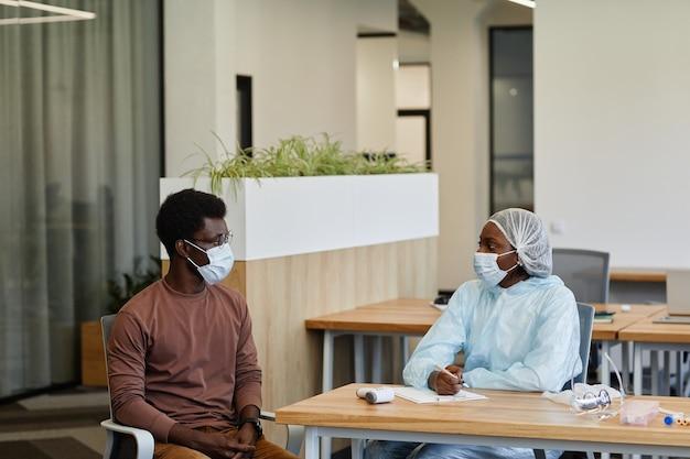 Pielęgniarka medyczna w kombinezonie ochronnym i masce medycznej rozmawia z pacjentem, zanim będzie mógł otrzymać szczepionkę przeciwko covid-19