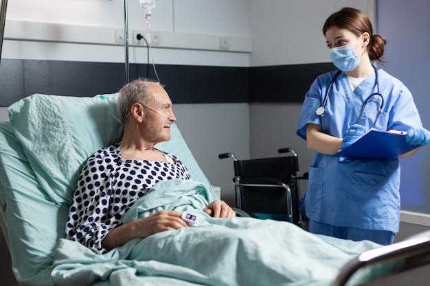 Pielęgniarka medyczna w peelingu z maską chirurgiczną robiąca notatki w schowku