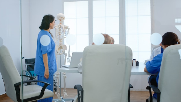 Pielęgniarka medyczna wskazująca na kręgosłup szyjny modelu anatomicznego ludzkiego szkieletu, wyjaśniająca współpracownikom procedury medyczne w sali konferencyjnej szpitala. lekarze rozmawiają o objawach choroby