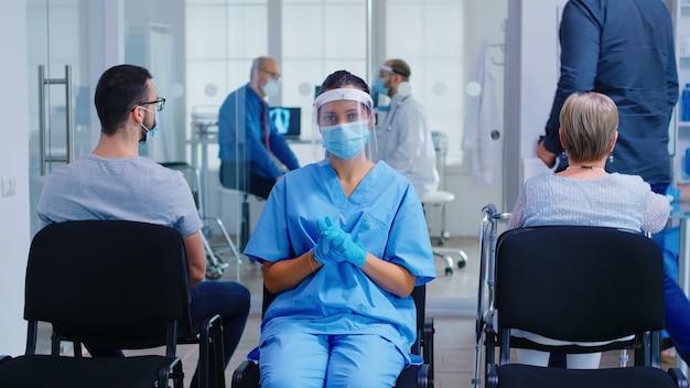 Pielęgniarka medyczna z maską i przyłbicą przeciwko koronawirusowi na sobie niebieski mundur w poczekalni szpitala. lekarz z starszym mężczyzną w sali egzaminacyjnej. niepełnosprawna dojrzała kobieta na wózku inwalidzkim.