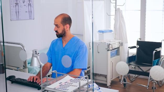 Pielęgniarka medyczny człowiek pisania na pc listy pacjenta i raport o stanie zdrowia, siedząc w biurze szpitala. lekarz opieki zdrowotnej w medycynie mundurowej wpisując zabiegi umawiając wizytę sprawdzając rejestrację.