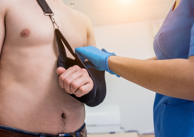 Pielęgniarka nakłada temblak na złamane ramię pacjenta. zranienie