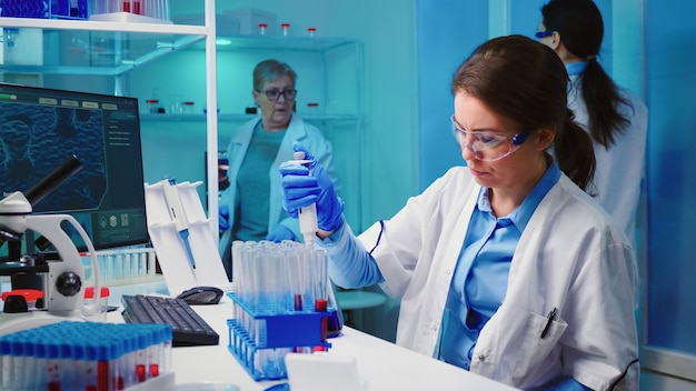 Pielęgniarka naukowa wykorzystująca mikropipetę do napełniania probówek w nowocześnie wyposażonym laboratorium pracująca w godzinach nadliczbowych