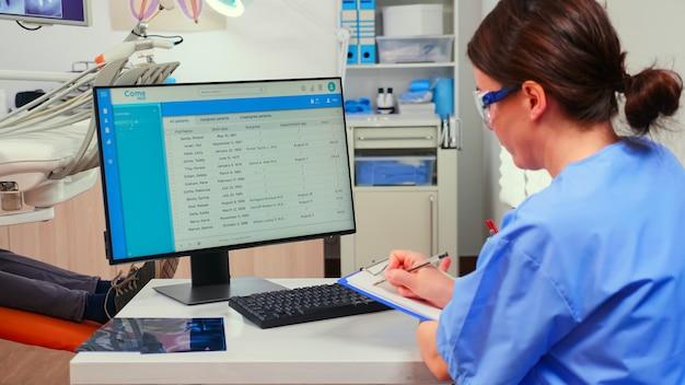 Pielęgniarka ortodonta patrząca na listę z wizytami w komputerze i robiąca notatki w schowku, podczas gdy lekarz stomatolog pracuje z pacjentem badając problemy z zębami.