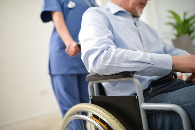 Pielęgniarka pcha rannego pacjenta na wózku inwalidzkim
