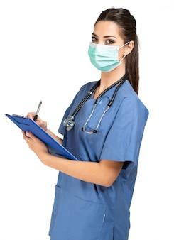 Pielęgniarka pisze dokumencie, odosobnionym na bielu