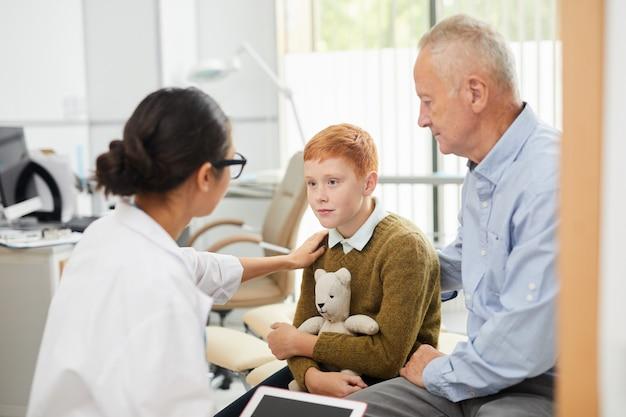 Pielęgniarka pociesza chłopca w biurze lekarzy