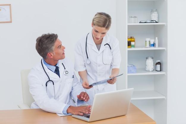Pielęgniarka pokazuje folder do swojego kolegi