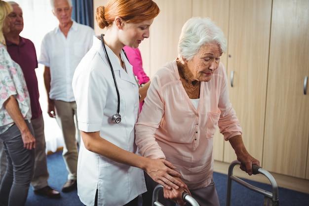 Pielęgniarka pomaga emerytowanej kobiecie chodzić