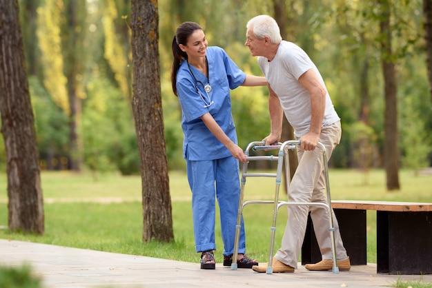 Pielęgniarka pomaga emerytowi chodzić po parku na dorosłych szczudłach