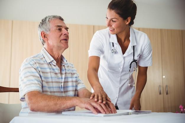 Pielęgniarka pomaga starszego mężczyzny z alfabetem braille'a