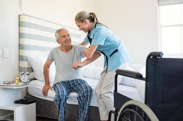 Pielęgniarka pomaga wstać starszemu pacjentowi