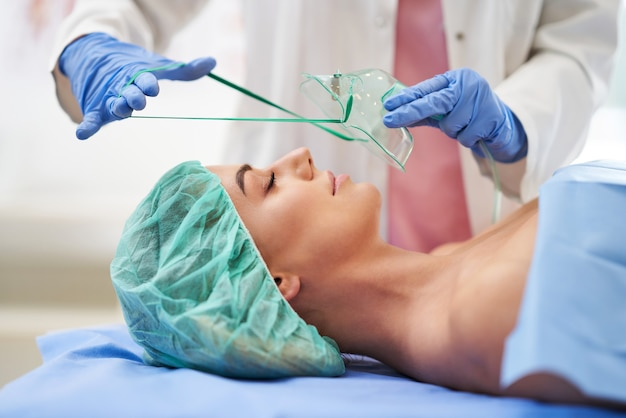 Pielęgniarka prowadzi terapię oddechową pacjentowi powracającemu do zdrowia w szpitalu.