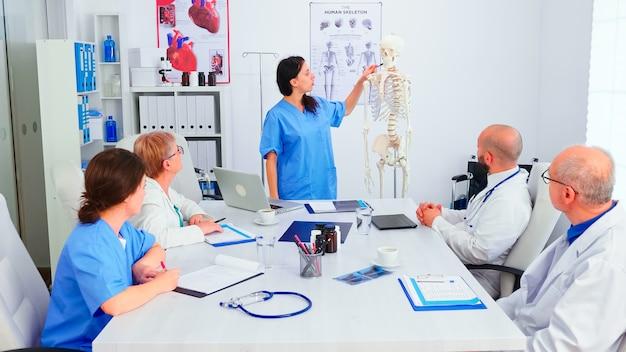 Pielęgniarka przedstawia przed zespołem lekarzy prezentację na temat anatomii człowieka z wykorzystaniem szkieletu. ekspert kliniczny terapeuta rozmawiający z kolegami o chorobie, specjalista od medycyny.