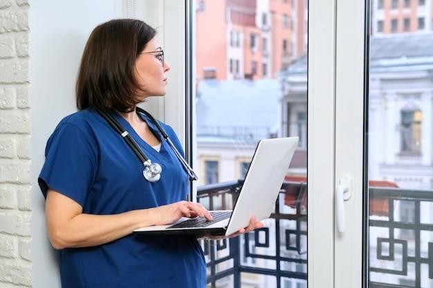 Pielęgniarka przy użyciu komputera przenośnego, lekarz w pobliżu okna w biurze kliniki.