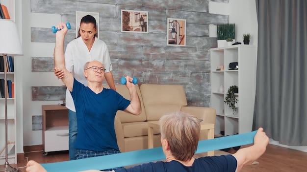 Pielęgniarka robi fizjoterapię z parą starszych. pomoc domowa, fizjoterapia, zdrowy styl życia dla osób starszych, trening i zdrowy styl życia