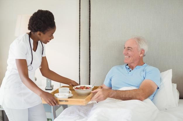 Pielęgniarka serwująca śniadanie starszemu pacjentowi
