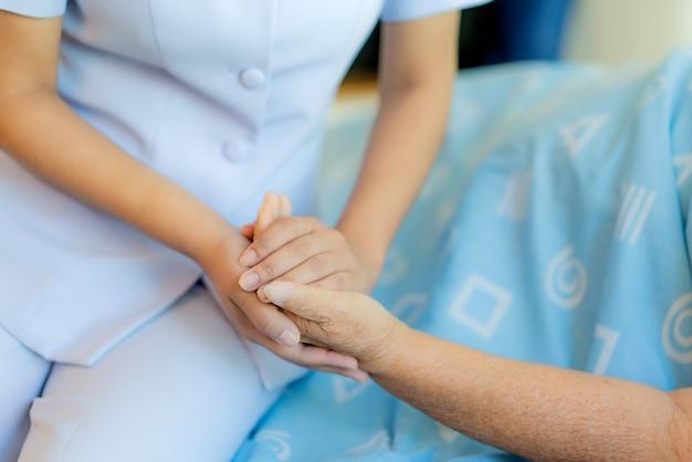Pielęgniarka siedzi na łóżku szpitalnym obok starszej kobiety pomagając ręce
