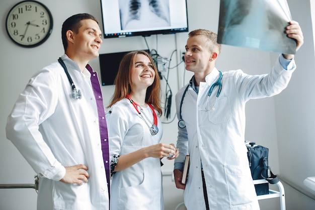 Pielęgniarka słucha lekarza studenci w szpitalnych fartuchach. mężczyźni i kobiety na oddziale szpitalnym.
