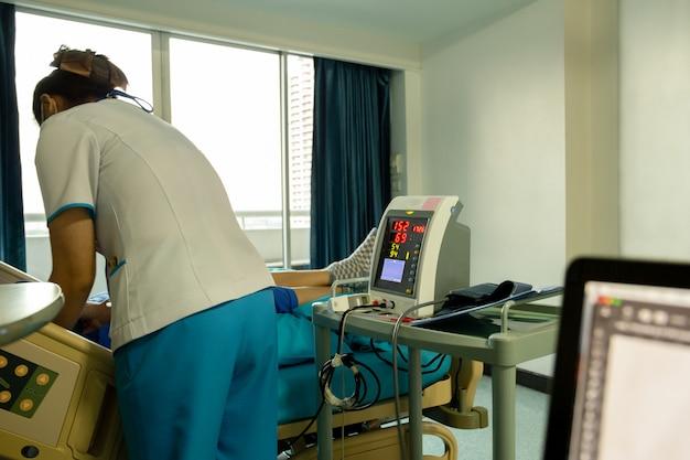 Pielęgniarka sprawdza ciśnienie krwi na monitoru ekranie dla cierpliwych zdrowie w szpitalu.