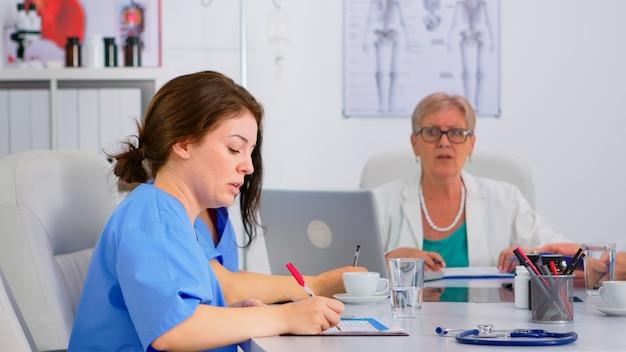 Pielęgniarka sprawdzająca listę pacjentów podczas burzy mózgów, dyskutująca z kolegami i robiąca notatki w schowku. zespół lekarzy rozmawiających o objawach choroby w gabinecie szpitalnym w tle.