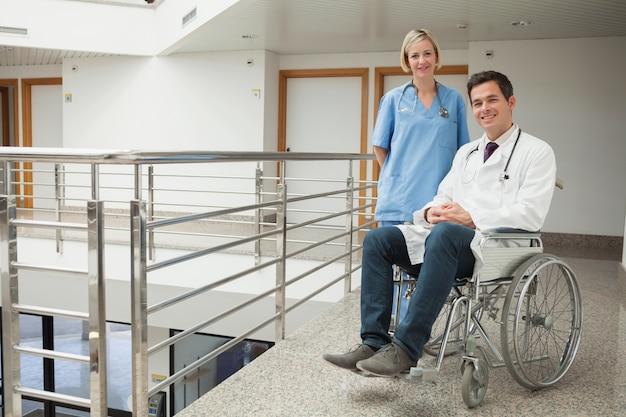 Pielęgniarka stałego z lekarzem siedzi na wózku inwalidzkim