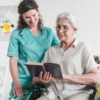 Pielęgniarka stojący za niepełnosprawne starszy kobieta czytanie książki