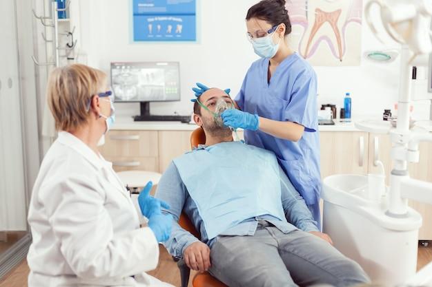 Pielęgniarka stomatolog zakładająca maskę tlenową przed operacją zęba siedząc na fotelu dentystycznym w gabinecie stomatologicznym