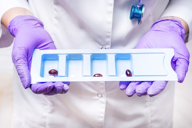 Pielęgniarka trzyma conteiner z lekiem, pigułką, witaminami