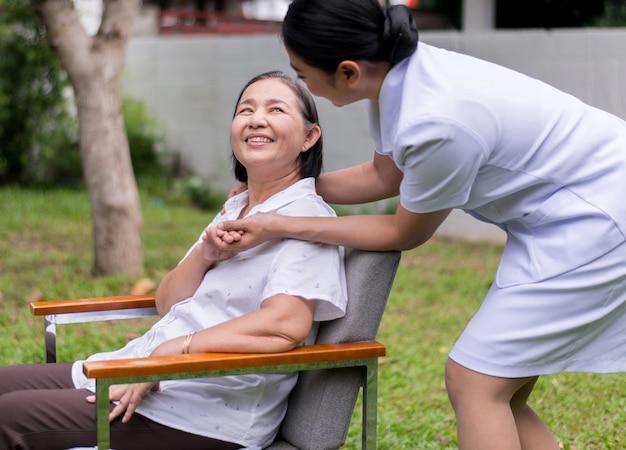 Pielęgniarka trzyma ręki starsza azjatycka kobieta z chorobą alzheimera, pozytywne myślenie, szczęśliwa i uśmiechnięta, opieki i wsparcia pojęcie