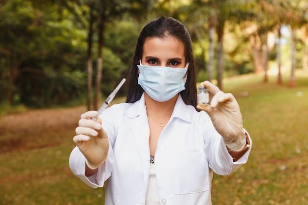 Pielęgniarka trzymająca szczepionkę covid 19 i strzykawkę. coronavac