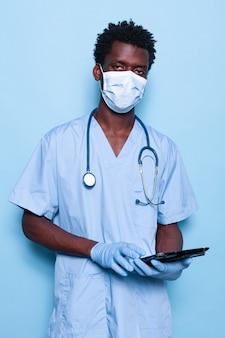 Pielęgniarka trzymająca tablet, patrząc na kamerę na białym tle