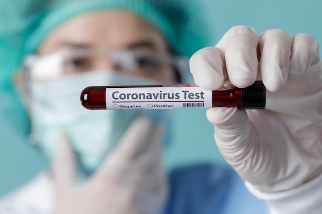 Pielęgniarka trzymająca w laboratorium próbki badanych próbek krwi na epidemię wirusa koronawirusa (covid-19), nowy koronawirus 2019-ncov