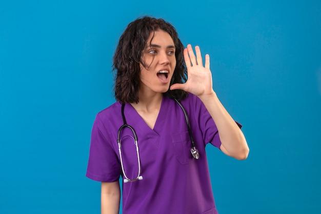 Pielęgniarka ubrana w mundur i stetoskop krzycząc wzywając kogoś ręką w pobliżu ust na na białym tle niebieski