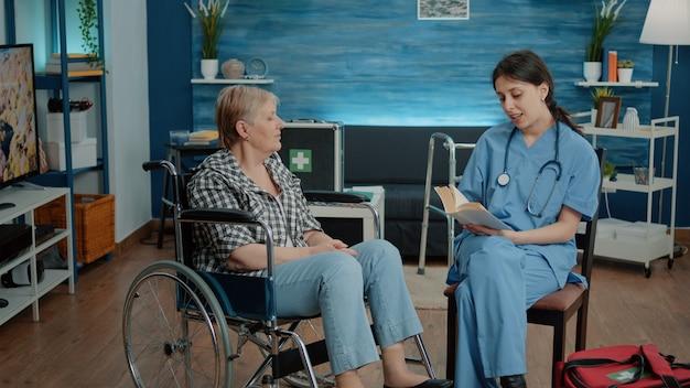 Pielęgniarka udzielająca pomocy emerytowanej kobiecie w domu opieki