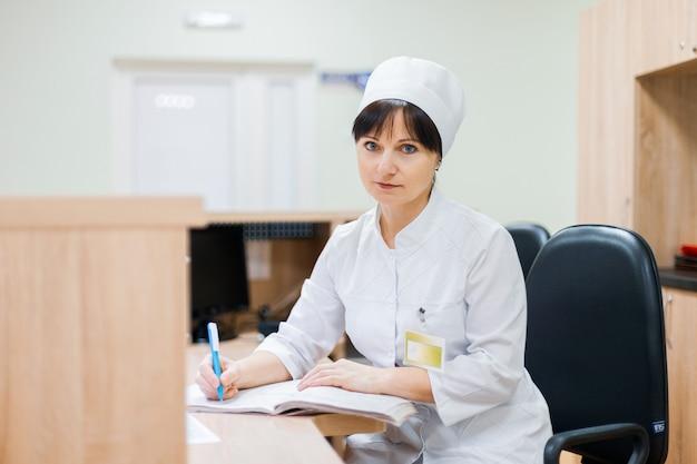 Pielęgniarka w białej fartuchu lekarskim siedzi przy drewnianym biurku w recepcji i dokonuje wpisów w dzienniku pracy. kobieta lekarz pracuje