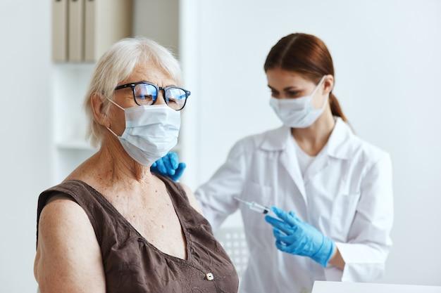 Pielęgniarka w białym fartuchu robi zastrzyk w ramię paszport ze szczepionką