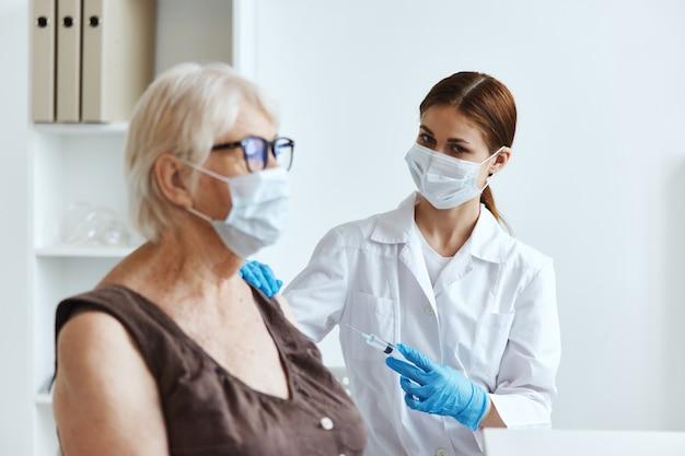 Pielęgniarka w białym fartuchu szczepienie starszej kobiety opieki zdrowotnej
