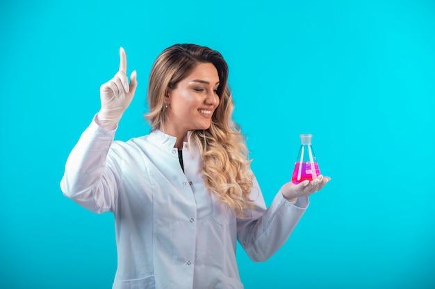Pielęgniarka w białym fartuchu trzymająca chemiczną kolbę z różowym płynem i prosi o uwagę.