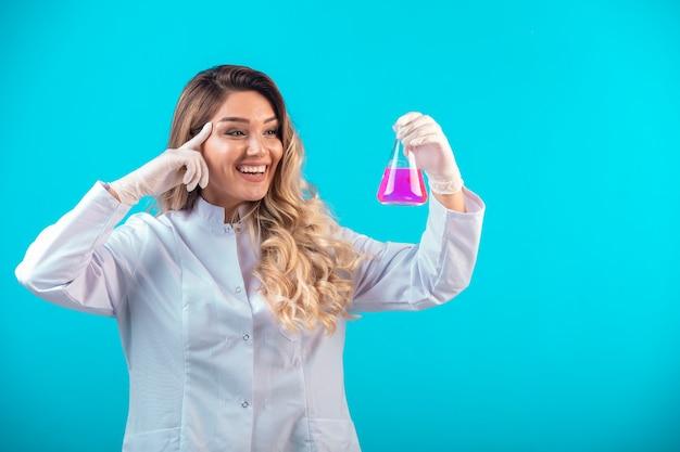Pielęgniarka w białym mundurze, trzymająca chemiczną kolbę z różowym płynem.