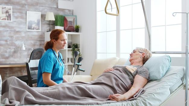 Pielęgniarka w domu starców rozmawia ze starszą panią leżącą w szpitalnym łóżku. z tyłu duże okna z jasnym światłem