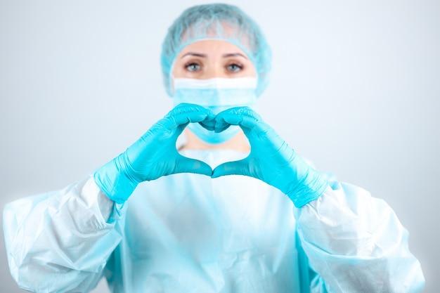 Pielęgniarka w fartuchu i masce medycznej wykonuje serdeczny gest palcami