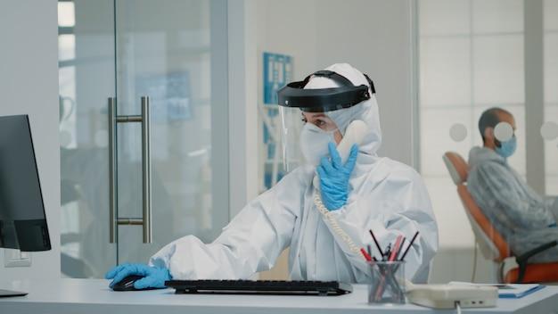 Pielęgniarka w garniturze ppe siedząca przy biurku kliniki higieny jamy ustnej