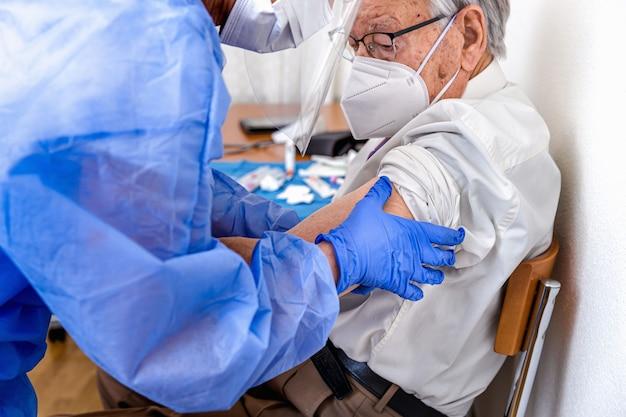 Pielęgniarka w kombinezonie ochronnym, masce i rękawiczkach przeciw koronawirusowi podwija rękawy koszuli starszego mężczyzny w masce do szczepień