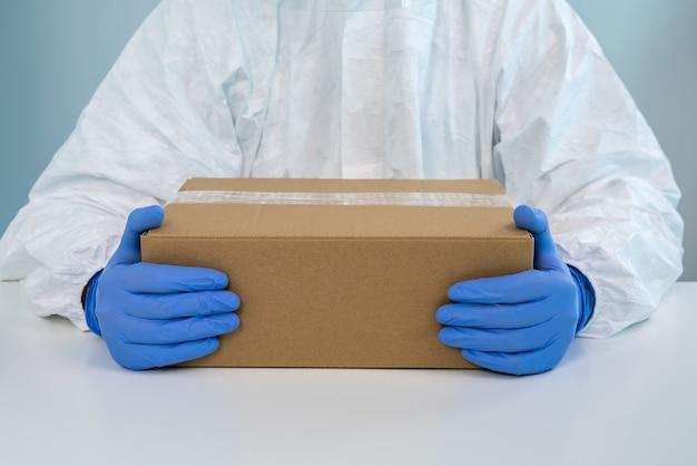 Pielęgniarka w kombinezonie ochronnym pokazuje w szpitalu pudełko z obiema rękami. pracownik służby zdrowia otrzymuje środki medyczne do walki z covid 19