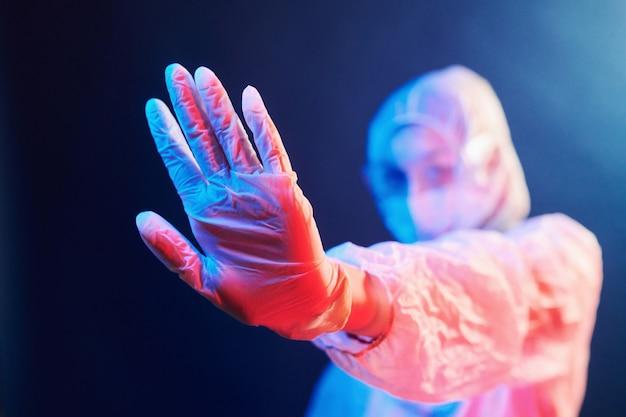 Pielęgniarka w masce i biały uniform stojący w oświetlonym pokoju neon i pokazując znak stop