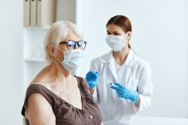 Pielęgniarka w masce medycznej robi zastrzyk w ramię paszport bezpieczeństwa szczepień ochronnych
