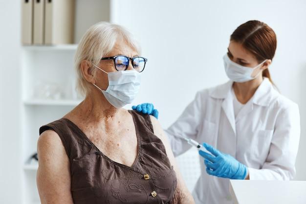 Pielęgniarka w masce medycznej robi zastrzyk w ramię paszport szczepionki