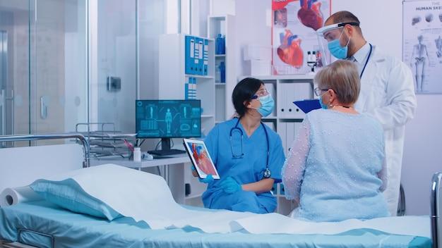 Pielęgniarka w masce z pacjentem kardiologicznym na wizytę u lekarza pokazującą reprezentację serca na cyfrowym tablecie w nowoczesnej klinice. lekarz wchodzący do pokoju szpitalnego rozmawiający ze starą emerytowaną pacjentką